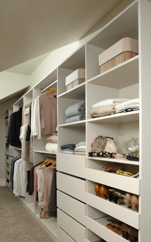 Moderno wardrobe along wall with sections for short and long hanging, drawers, open shelves and pull out shoe shelves.