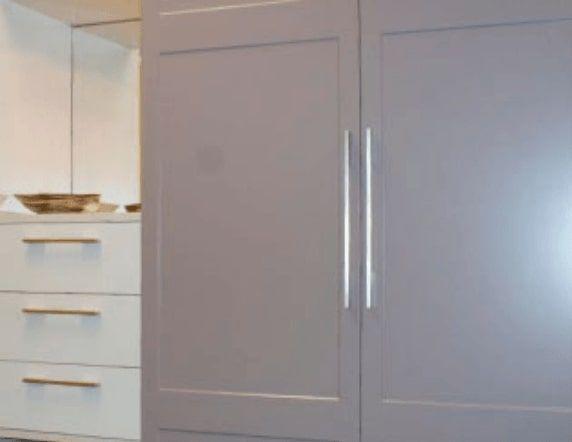 Wardrobe doors in grey with long vertical silver door handles.
