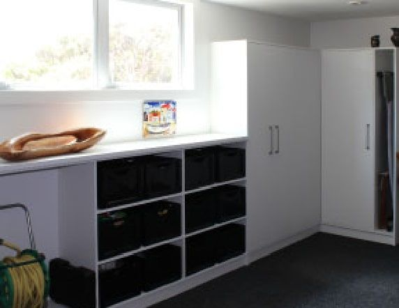 White tall cabinets and shelves with bench space built into a garage.