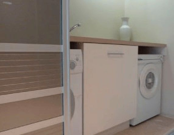 Bench, cabinets and sliding doors built into a small tidy laundry space
